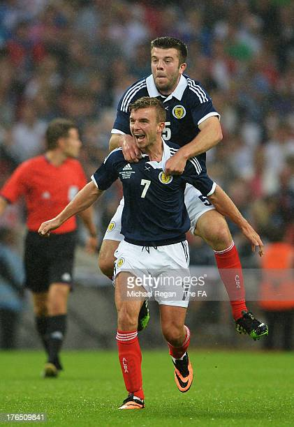 James Morrison of Scotland celebrates scoring the opening goal with team mate Grant Hanley during the International Friendly match between England...