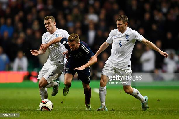 James Morrison of Scotland is closed down by Jack Wilshere of England and James Milner of England during the International Friendly match between...