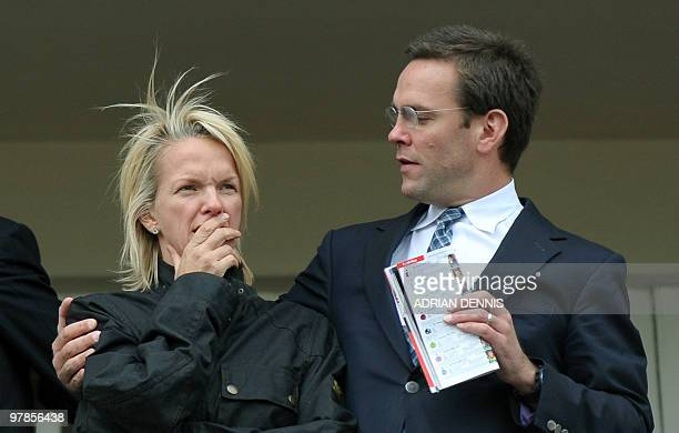 James Murdoch son of media mogul Rupert Murdoch gestures toward his sister Elisabeth Murdoch as they stand in a balcony overlooking the racing during...