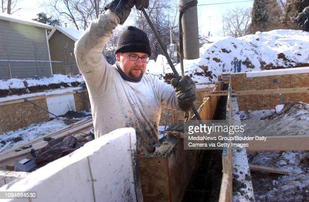 James Nasty of Done Wright Builders mixes poured concrete as they wait for the next concrete truck at the home site of Julie Maren and Derek van...