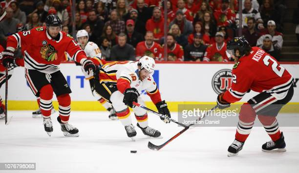 James Neal of the Calgary Flames chases down the puck between Artem Anisimov and Duncan Keith of the Chicago Blackhawks at the United Center on...