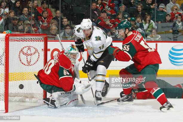 James Neal of the Dallas Stars shoots wide with Jose Theodore and Nick Schultz of the Minnesota Wild defending during the game at Xcel Energy Center...