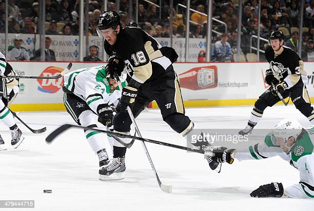 James Neal of the Pittsburgh Penguins breaks through the defense of Jordie Benn and Brenden Dillon of the Dallas Stars on March 18 2014 at Consol...