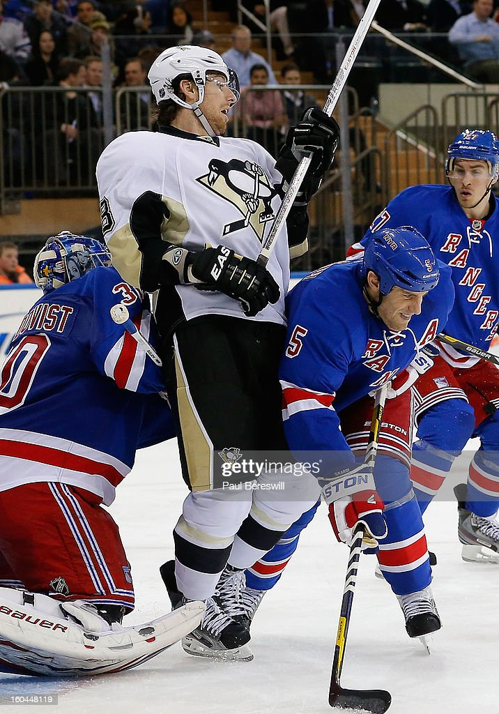 James Neal #18 of the Pittsburgh Penguins is checked by Dan Girardi #5 of the New York Rangers as goalie Henrik Lundqvist #30 Rangers blocks the goal in the third period of an NHL hockey game at Madison Square Garden on January 31, 2013 in New York City.