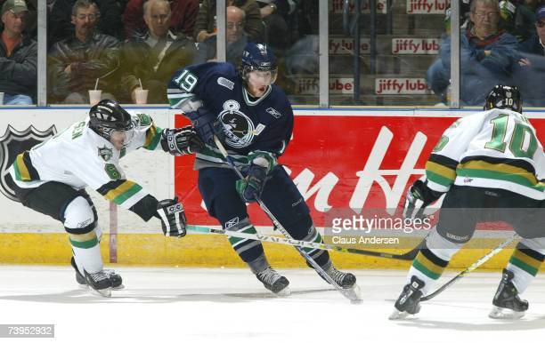 James Neal of the Plymouth Whalers skates with the puck between Scott Aarssen and Josh Beaulieu of the London Knights in game one of the Western...