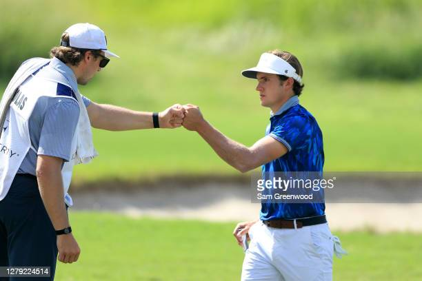 James Nicholas fist bumps his caddie Charlie McAvoy of the Boston Bruins on the 17th hole during the first round of the Orange County National...