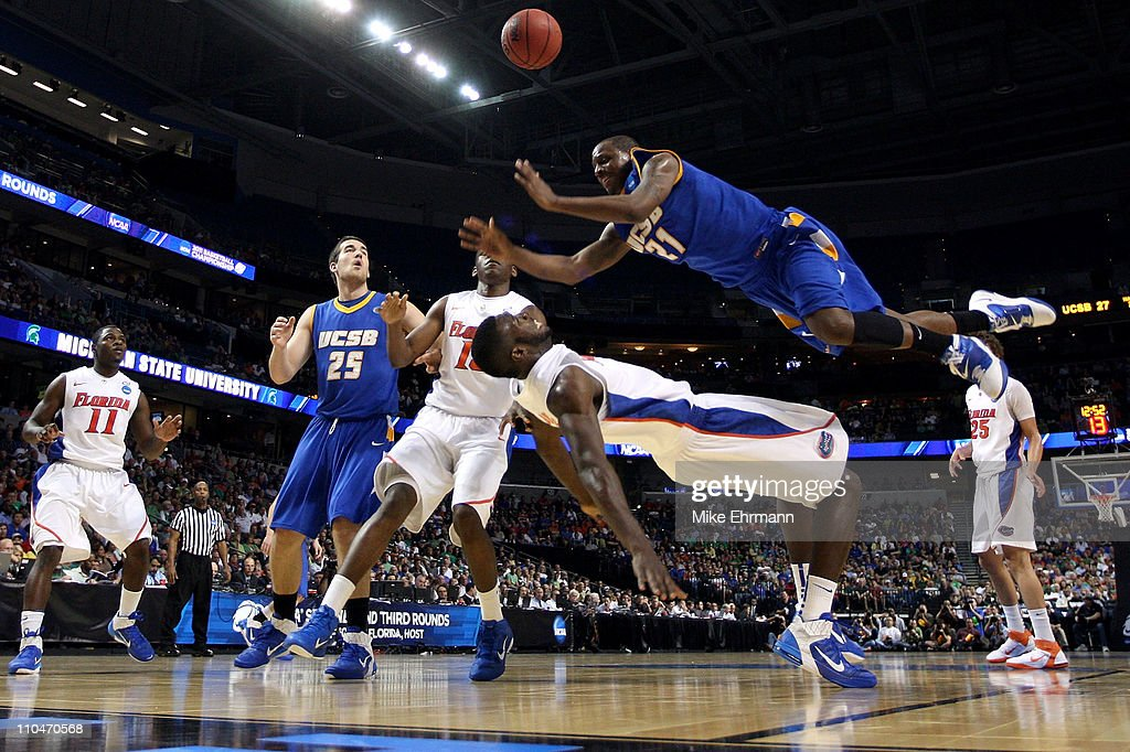 James Nunnally #21 of the UC Santa Barbara Gauchos falls as he loses the ball driving against Patric Young #4 of the Florida Gators in the second half during the second round of the 2011 NCAA men's basketball tournament at St. Pete Times Forum on March 17, 2011 in Tampa, Florida.