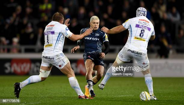 James O'Connor of Sale kicks between Carl Rimmer and Thomas Waldrom of Exeter during the Aviva Premiership match between Sale Sharks and Exeter...