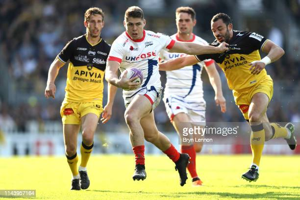 James O'Connor of Sale Sharks is held by Geoffrey Doumayrou of Stade Rochelais during the Challenge Cup Semi Final match between La Rochelle and Sale...