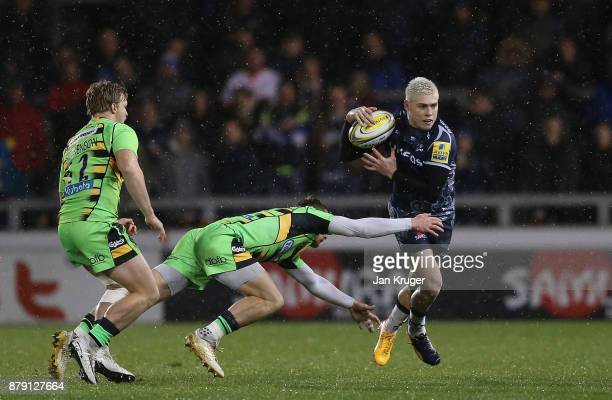 James O'Connor of Sale Sharks slips through the tackle of Roy Hutchinson of Northampton during the Aviva Premiership match between Sale Sharks and...