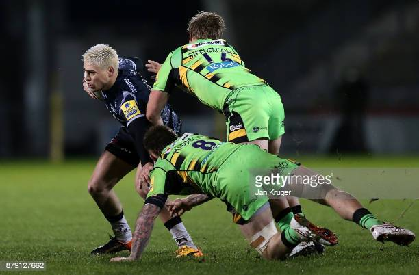 James O'Connor of Sale Sharks slips through the tackle of Teimana Harrison and Tom Stephenson of Northampton during the Aviva Premiership match...