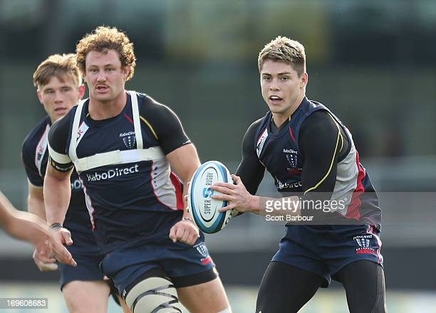 James O'Connor of the Rebels runs with the ball as Jason Woodward and Scott Higginbotham look on during a Melbourne Rebels Super Rugby training...