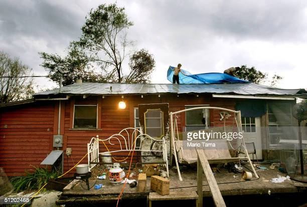 James O'Neil and his father Hank Williams place a tarp over their his damaged trailer home roof as a storm approaches August 21 2004 in Arcadia...