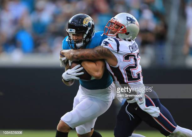 James O'Shaughnessy of the Jacksonville Jaguars is tackled by Patrick Chung of the New England Patriots in the first half at TIAA Bank Field on...