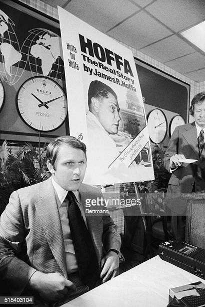 James P Hoffa Jr son of the missing exTeamsters' official sits beneath a poster of his father as he talks to reporters at the Overseas Press Club...