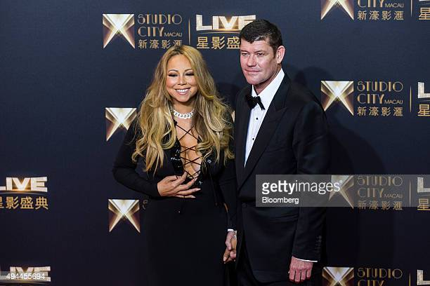James Packer cochairman of Melco Crown Entertainment Ltd right and singer Mariah Carey stand for photographs at the red carpet event prior to the...