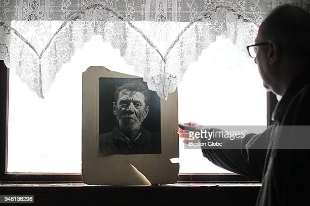 James Pantages reaches for one of his collected artworks resting in a window of his home in Quincy MA on April 2 2018 For many years Pantages spent...