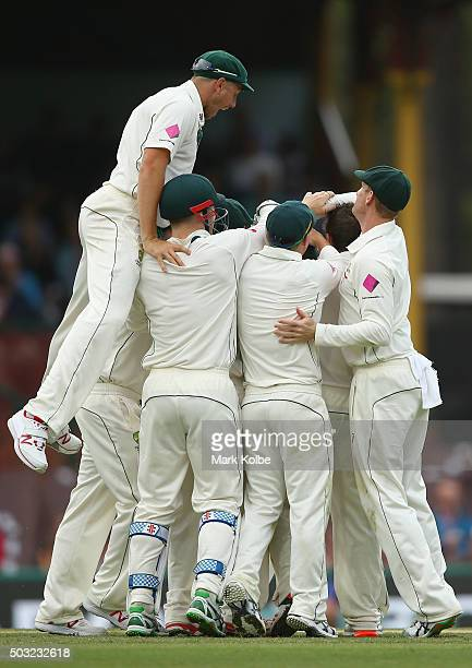 James Pattinson of Australia jumps to join his team mate congratulate Joe Burns of Australia as he celebrates taking the catch to dismiss Jason...