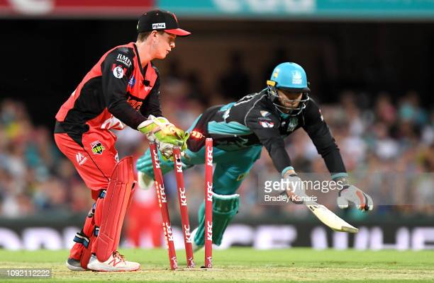 James Pattinson of the Heat is caught short of his ground by wicketkeeper Sam Harper of the Renegades during the Big Bash League match between the...