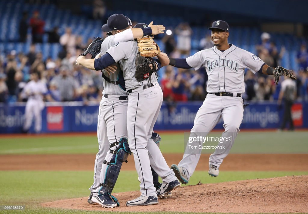 James Paxton #65 of the Seattle Mariners celebrates his no-hitter with Mike Zunino #3 as Jean Segura #2 runs to greet them during MLB game action against the Toronto Blue Jays at Rogers Centre on May 8, 2018 in Toronto, Canada.