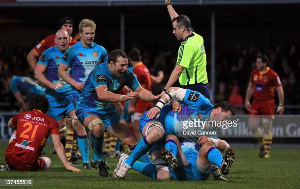 James Phillips of Exeter Chiefs scores Exeter's third try as Simon Alcott rolls him over two right blue players as other Exeter players begin to...