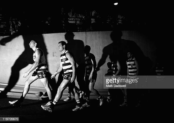 James Podsiadly and Josh Hunt of the Cats lead the team out for the round 18 AFL match between the Geelong Cats and the Richmond Tigers at Etihad...