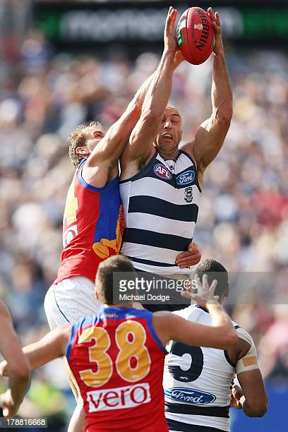 James Podsiadly of the Cats marks the ball against Joel Patfull of the Lions during the round 23 AFL match between the Geelong Cats and the Brisbane...