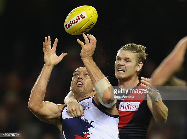 James Podsiadly of the Crows and Michael Hurley of the Bombers compete for the ball during the round 14 AFL match between the Essendon Bombers and...
