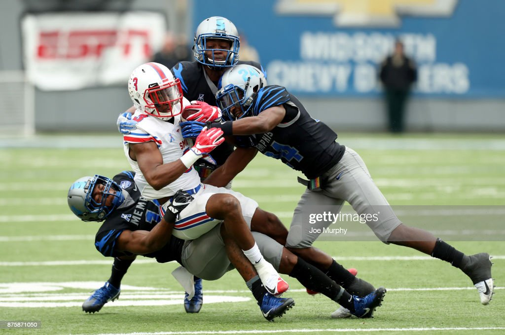James Proche #3 of the SMU Mustangs is tackled by Jonathan Cook #14 and Tito Windham #24 of the Memphis Tigers on November 18, 2017 at Liberty Bowl Memorial Stadium in Memphis, Tennessee.