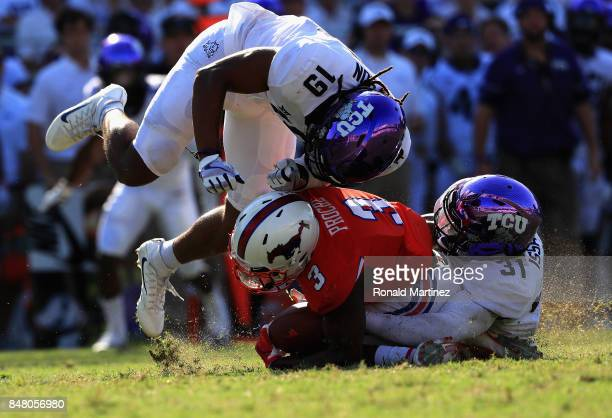 James Proche of the Southern Methodist Mustangs is tackled by Montrel Wilson and Ridwan Issahaku of the TCU Horned Frogs in the second half at Amon G...