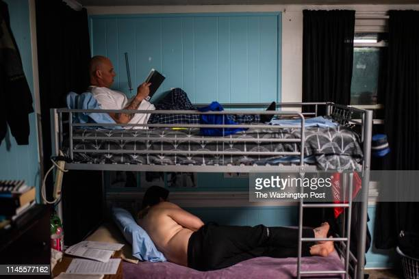 James Proffit reads The Big Book of Alcoholics Anonymous before going to bed at Sojourner Recovery's campus a treatment facility on Wednesday April 3...