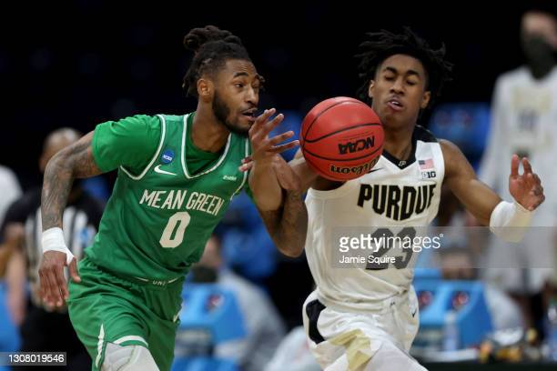 James Reese of the North Texas Mean Green and Jaden Ivey of the Purdue Boilermakers battle for a loose ball in overtime in the first round game of...