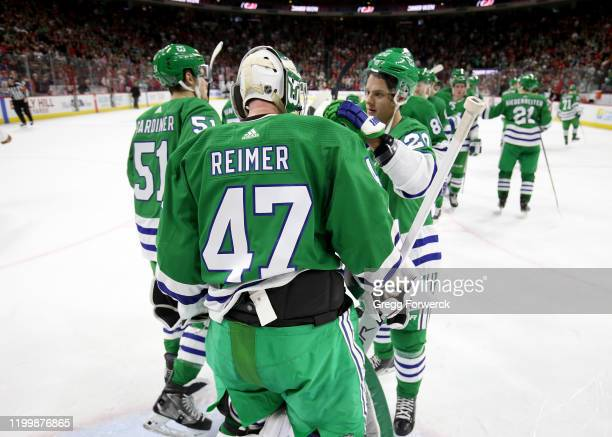 James Reimer of the Carolina Hurricanes gets a shutout victory and is congratulated by teammate Sebastian Aho during an NHL game against the Los...
