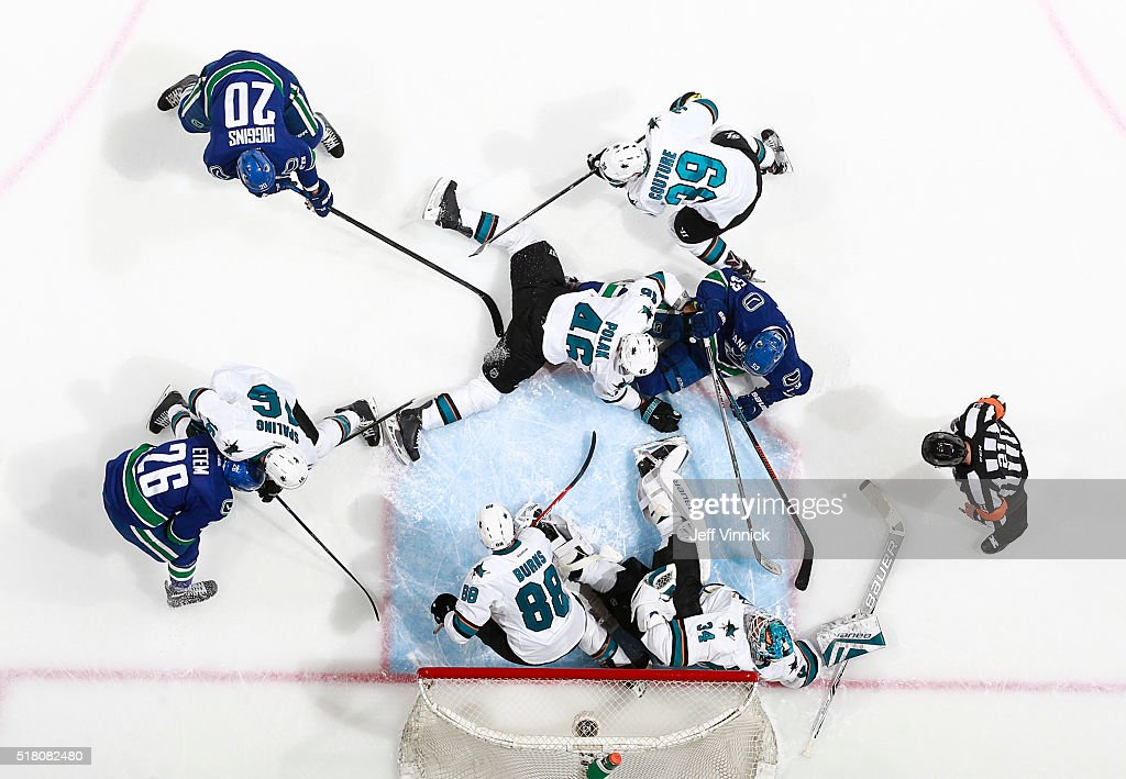 James Reimer of the San Jose Sharks sprawls in a crowd of players to make a save during their NHL game at Rogers Arena March 29, 2016 in Vancouver, British Columbia, Canada. San Jose won 4-1.