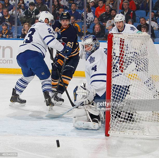 James Reimer of the Toronto Maple Leafs makes a save as teammate Trevor Smith defends against Tyler Ennis of the Buffalo Sabres on November 29 2013...