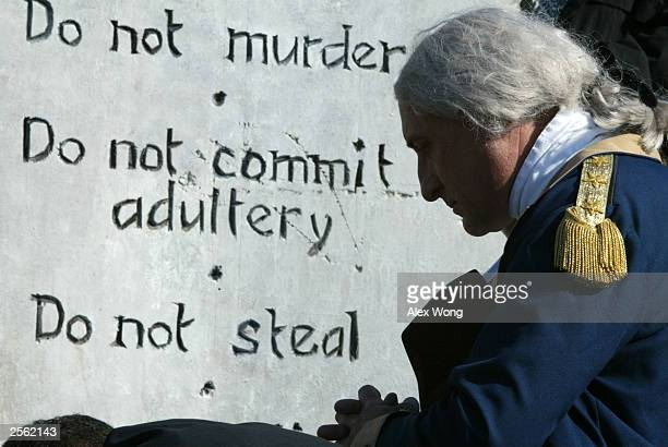 James Renwick Manship of Mt Vernon Virginia dresses as George Washington as he prays in front of a display of a Ten Commandments monument October 5...