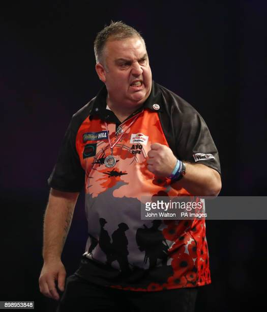 James Richardson celebrates taking the opening set against Alan Norris during day eleven of the William Hill World Darts Championship at Alexandra...