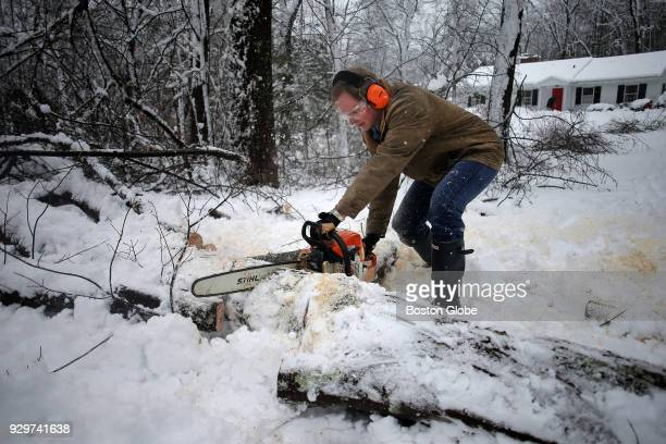 James Richardson cuts apart a tree blocking his parents' driveway in Acton MA after it was brought down by a nor'easter storm on March 8 2018