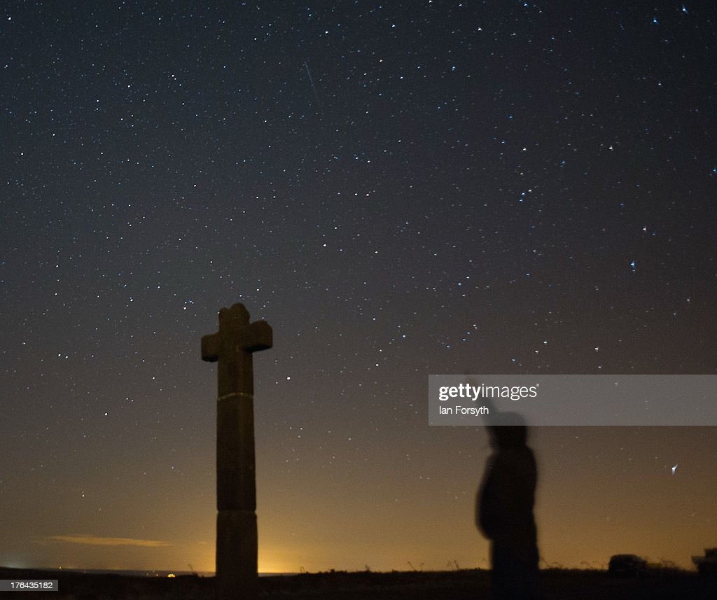 James Ritson points skywards as a meteor streaks across the night sky above New Ralph's Cross on August 13, 2013 over the North Yorkshire Moors, United Kingdom. The Perseid Meteor shower is visible from mid-july each year with peak activity being between the 9th and 14th of August. During the peak, the rate of meteors can reach 60 or more per hour. They can be seen all across the sky as they gradually fall away from the tail of the Swift-Tuttle comet.