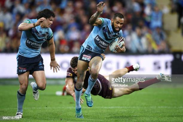 James Roberts of the Blues watches on as Josh AddoCarr of the Blues beats the tackle of Corey Oates of Queensland during game three of the State of...