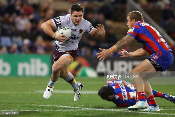 James Roberts of the Broncos is tackled during the round 19 NRL match between the Newcastle Knights and the Brisbane Broncos at McDonald Jones...