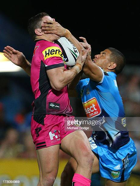 James Roberts of the Panthers catches a high ball against David Mead of the Titans and scores a try during the round 17 NRL match between the Gold...