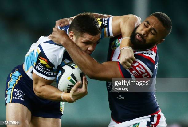James Roberts of the Titans puts a fend on Michael Jennings of the Roosters during the round 22 NRL match between the Sydney Roosters and the Gold...