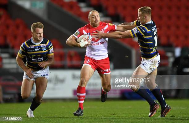 James Roby of St Helens breaks through the contact of Brad Dwyer and Mikolaj Oledzki of Leeds Rhinos during the Betfred Super League match between St...