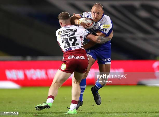 James Roby of St Helens is tackled by Amir Bourouh of Wigan Warriors during the Betfred Super League match between Wigan Warriors and St Helens at AJ...