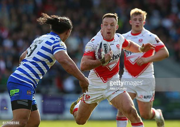 James Roby of St Helens is tackled by Taulima Tautai of Wigan Warriors during the First Utility Super League match between St Helens and Wigan...