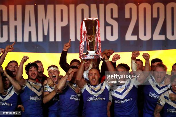 James Roby of St Helens lifts the trophy as his team mates celebrate victory following the Betfred Super League Grand Final between Wigan Warriors...