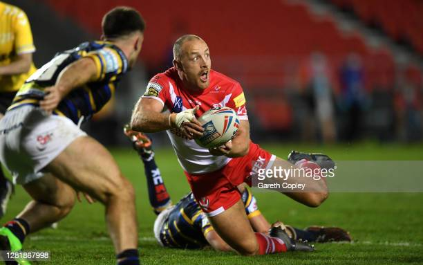 James Roby of St Helens looks to pass after being tackled by Jack Walker of Leeds Rhinos during the Betfred Super League match between St Helens and...