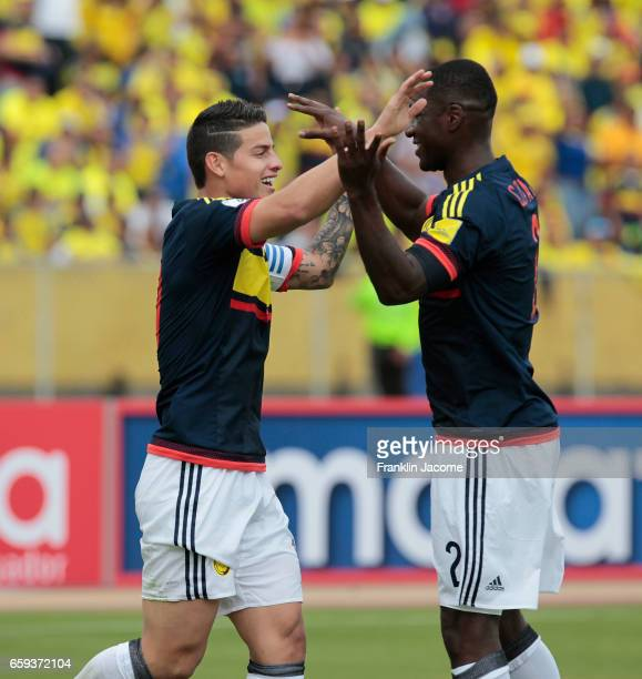 James Rodríguez of Colombia celebrates with teammate Cristian Zapata after scoring the first goal of his team during a match between Ecuador and...