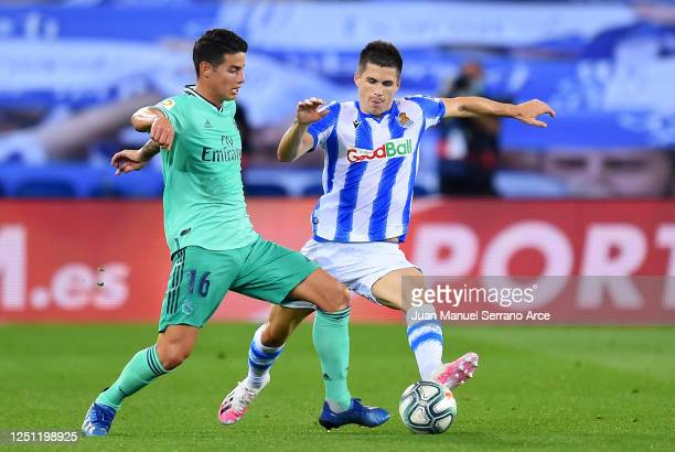 James Rodríguez of Real Madrid is tackled by Igor Zubeldia of Real Sociedad during the Liga match between Real Sociedad and Real Madrid CF at Estadio...